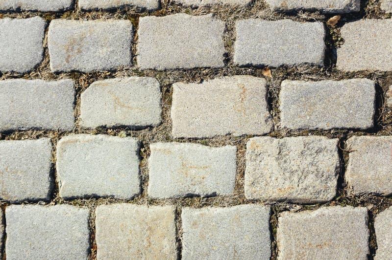 Piastrellato con il frammento del percorso dei mattoni di pietra per lastricati come fondo astratto fotografia stock libera da diritti