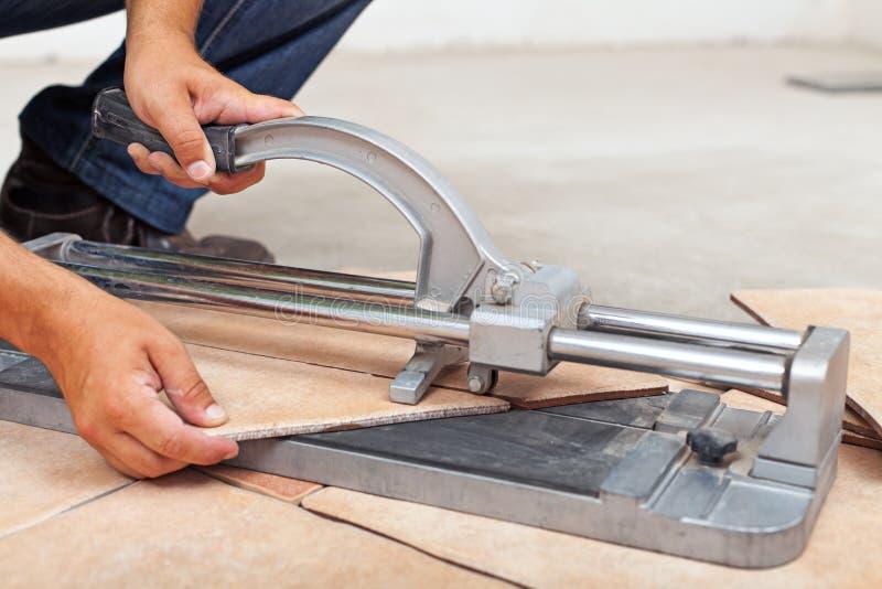 Piastrelle per pavimento di taglio del lavoratore con la taglierina manuale fotografie stock libere da diritti