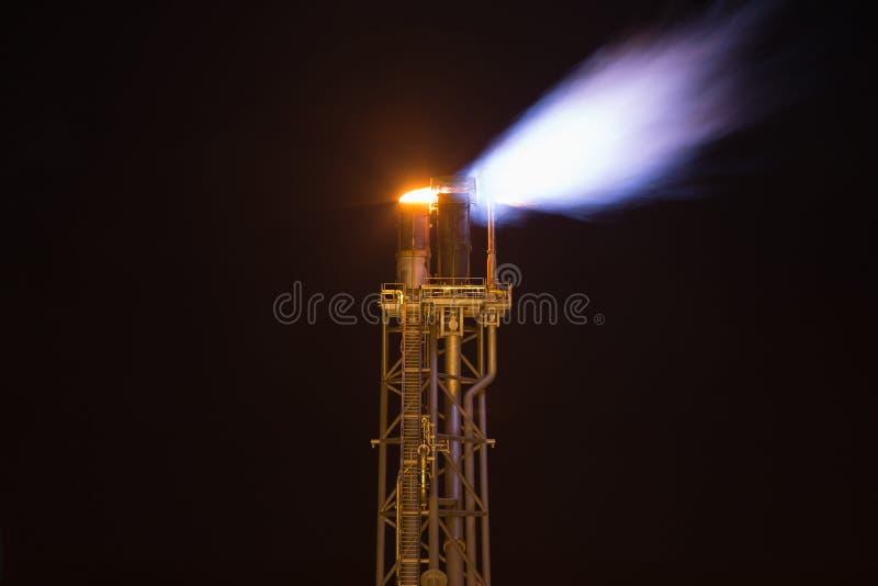 Piattaforma della fiaccola mentre gas brucianti dall'elaborazione al platfom del gas e del petrolio per impedire sopra pressione  fotografia stock