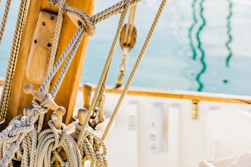 Piattaforma di barca a vela tradizionale, corde nautiche legate d'attrezzatura sui morsetti sull'albero di legno fotografie stock