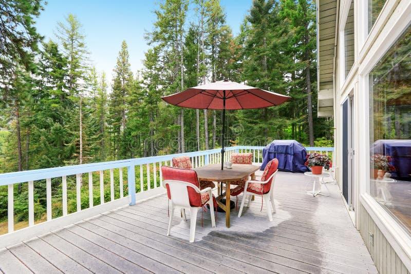 Piattaforma di legno dell'uscire in segno di disapprovazione dopo pioggia Ammobiliato di sedie e di tavola rosse con l'ombrello fotografia stock libera da diritti