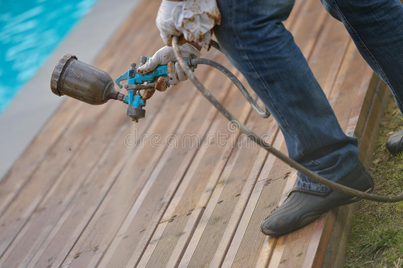 Piattaforma di legno di spruzzatura con la pistola a spruzzo fotografia stock