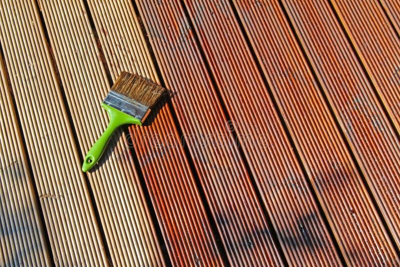 Piattaforma di legno di verniciatura del patio con olio protettivo fotografia stock