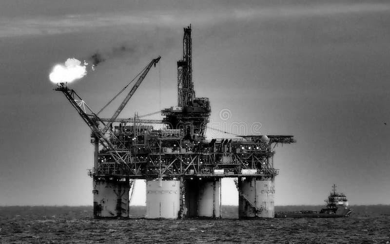 Piattaforma petrolifera o impianto di perforazione scintillante in mare fotografie stock libere da diritti