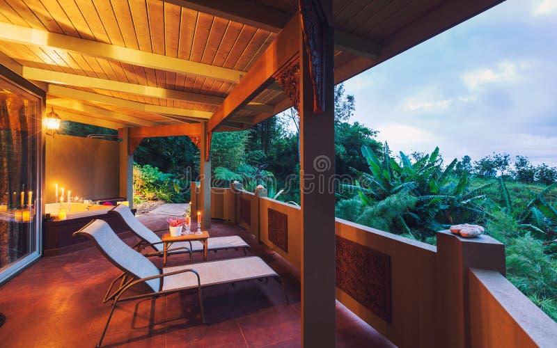 Piattaforma romantica sulla casa tropicale al tramonto immagine stock