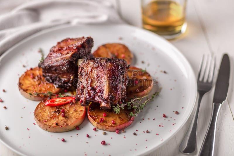 Piatti caldi della carne Costole di carne di maiale grigliate con i peperoni e le mele fotografia stock libera da diritti