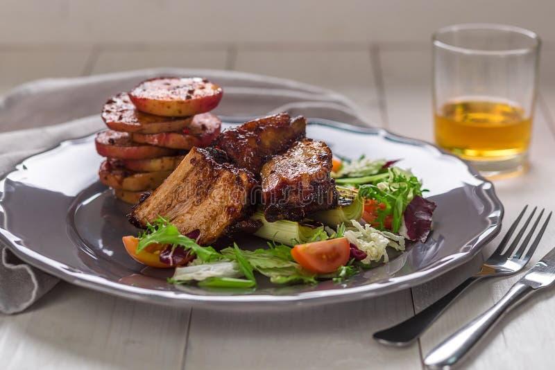 Piatti caldi della carne Le costole di carne di maiale hanno grigliato con insalata e le mele su un piatto fotografie stock libere da diritti