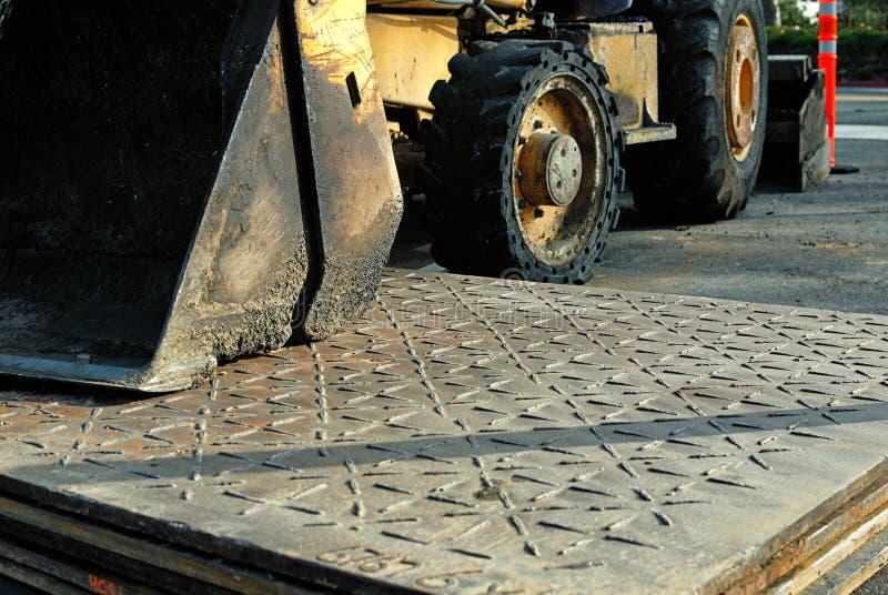 Piatti d'acciaio utilizzati nella costruzione di strade con un bulldozer del toro nei precedenti immagini stock libere da diritti