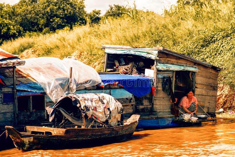 Piatti del lavaggio della donna in casa di galleggiamento sul lago sap di Tonle fotografia stock
