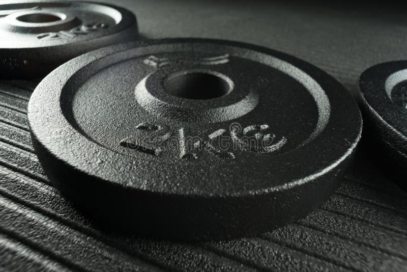 Piatti del peso della testa di legno su un pavimento della palestra di addestramento del peso fotografia stock libera da diritti