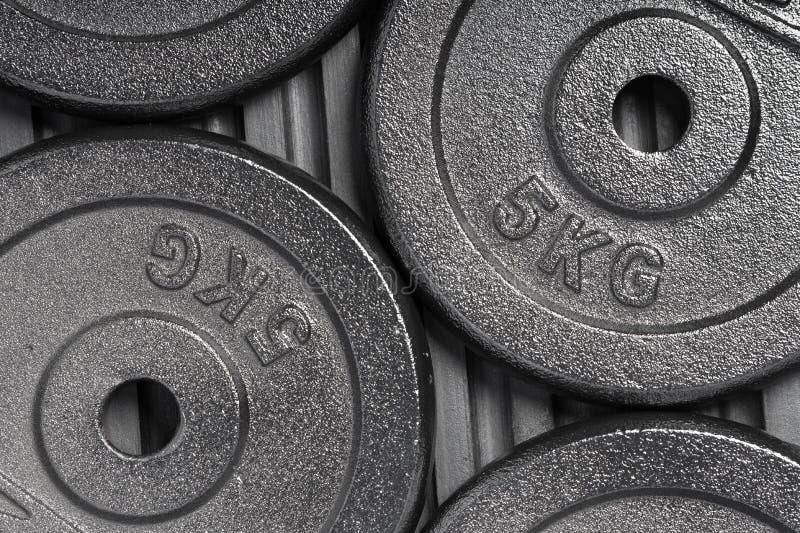 Piatti del peso su un pavimento di gomma nero dentro una palestra di addestramento del peso immagini stock