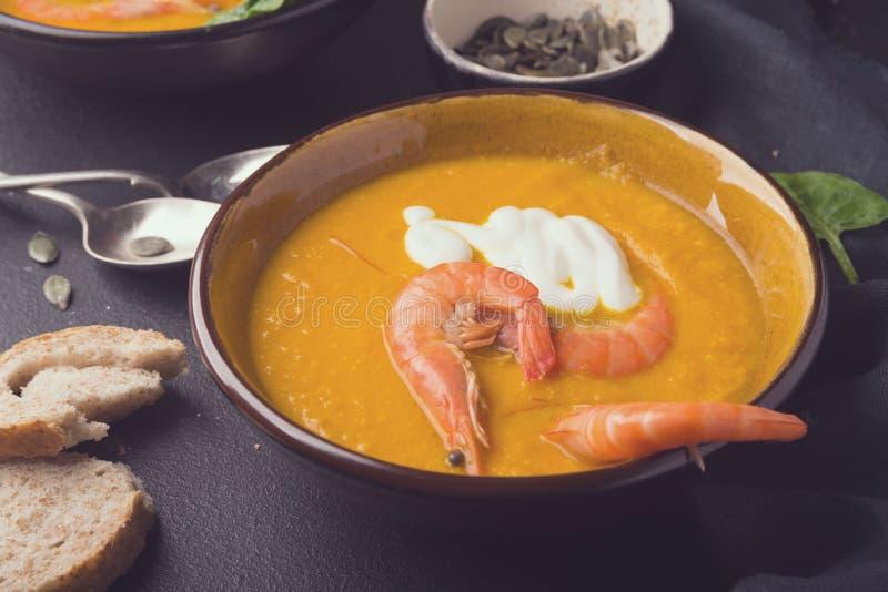 2 piatti della minestra arancio della zucca su una tavola nera Tre gamberetti rossi decorano la minestra immagine stock
