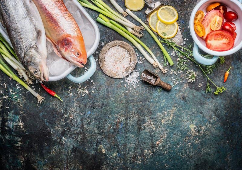 Piatti di pesce che cucinano preparazione con l'interi pesce della trota e trota iridea ed ingredienti crudi dell'oro su fondo ru fotografia stock libera da diritti