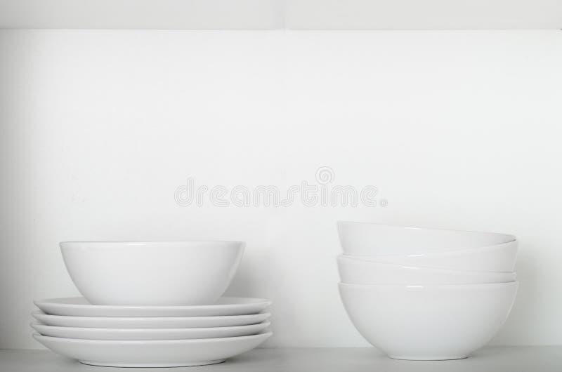 Piatti e ciotole bianchi su uno scaffale nell'armadietto Articolo da cucina, piatti puliti immagine stock libera da diritti