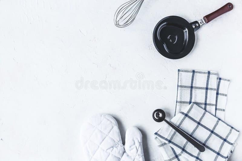 Piatti ed accessori della cucina per cuocere sul tavolo da cucina su un fondo bianco fotografia stock libera da diritti