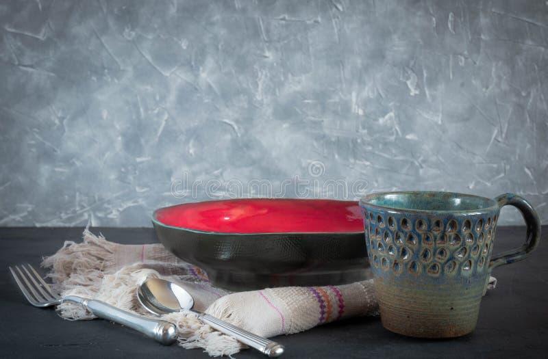 Piatti fatti a mano dell'argilla dei colori differenti su calcestruzzo nero piatti, tazze tagliere antico immagine stock