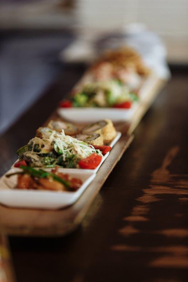 Piatti giapponesi assortiti in piatti quadrati bianchi sui supporti di legno sui precedenti della tavola fotografia stock