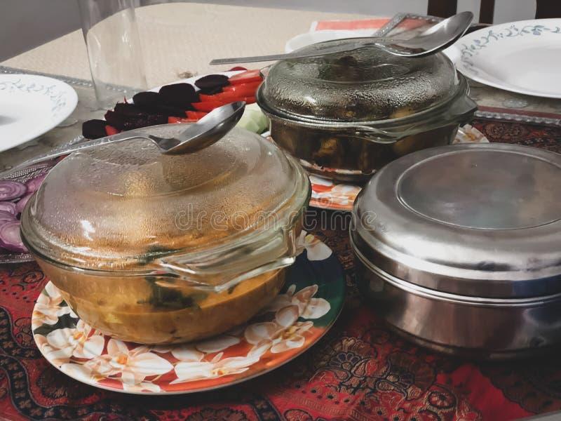 Piatti indiani pronti dell'alimento in contenitori su un tavolo da pranzo a casa indiana fotografia stock libera da diritti