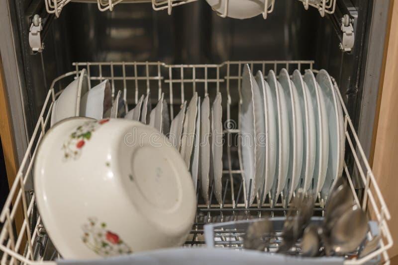 Piatti nel canestro di una lavastoviglie, pronto per la pulizia, fuoco selezionato, profondità di campo molto stretta Apra la lav fotografia stock libera da diritti