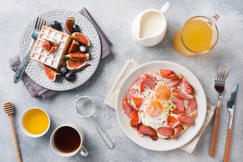 Piatti per la cottura a casa di uova fritte alla colazione con salsicce e pomodori waffe fluciate belghe con fichi e uve Grigio fotografia stock