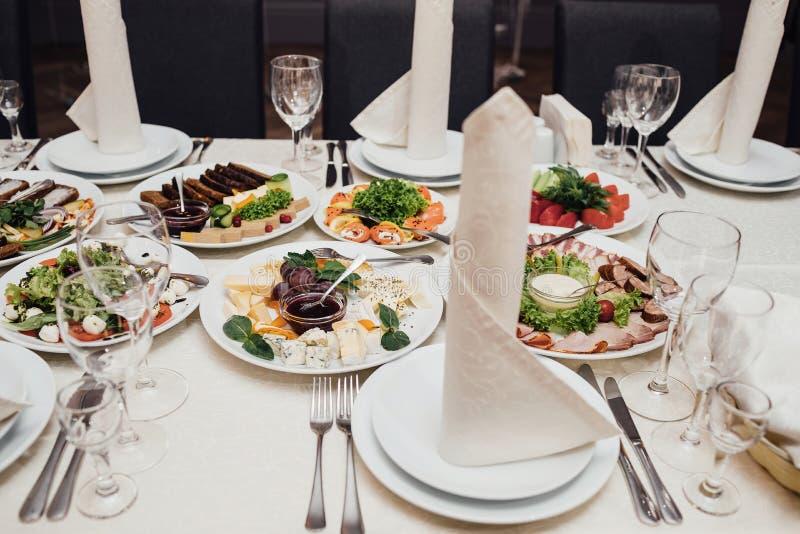 Piatti serviti alla tavola per la festa immagine stock
