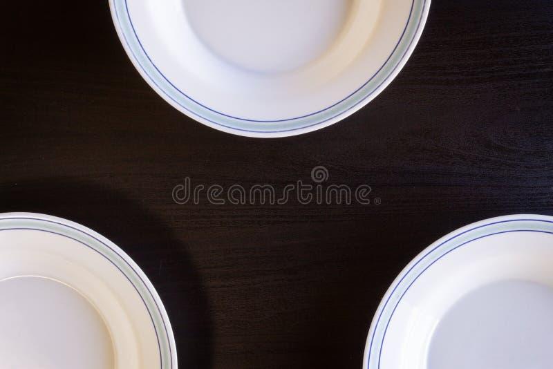 Piatti vuoti su fondo di legno nero fotografie stock