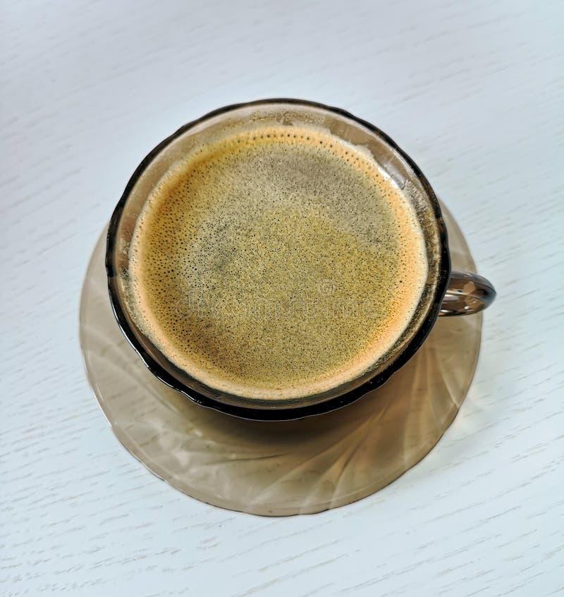 Piattino e tazza di vetro marrone temperato con il supporto del caffè nero su una tavola di legno bianca immagini stock libere da diritti