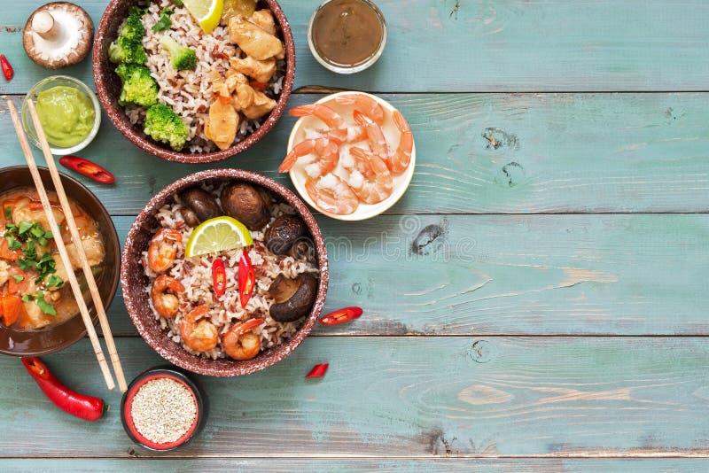 Piatto asiatico, riso, gamberetto, funghi, pollo su un fondo rustico di legno blu Vista superiore, spazio della copia fotografia stock libera da diritti