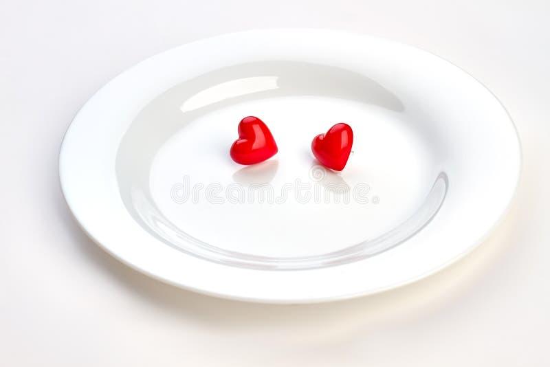 Piatto bianco con due cuori rossi fotografia stock