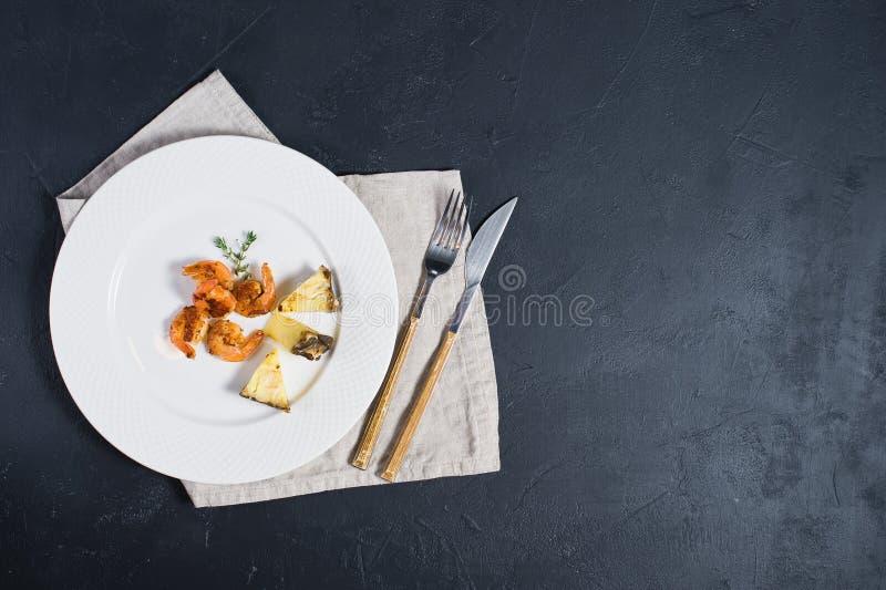 Piatto bianco con i gamberetti fritti di re su fondo nero con spazio per testo fotografia stock libera da diritti