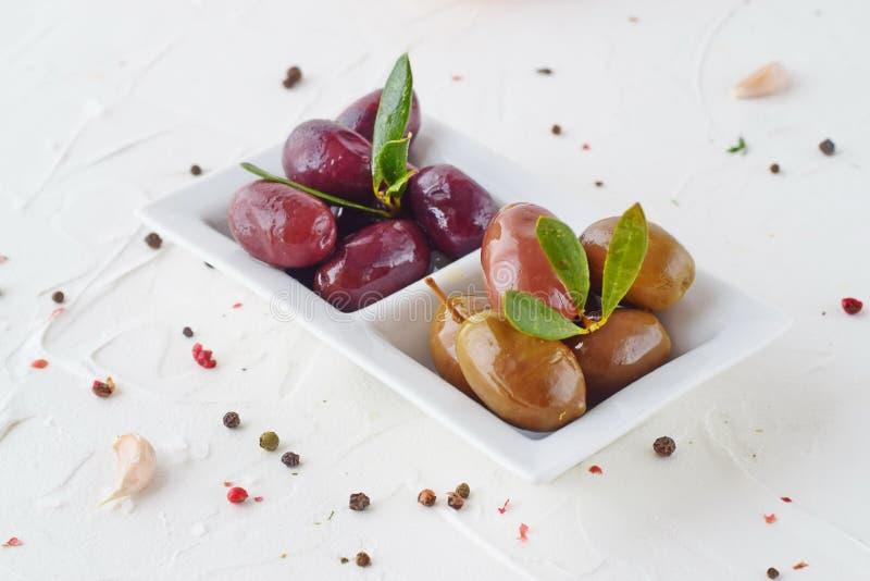 Piatto bianco con le olive nere e verdi con le foglie verde oliva su un fondo astratto bianco con il limone, pomodoro ciliegia fotografie stock