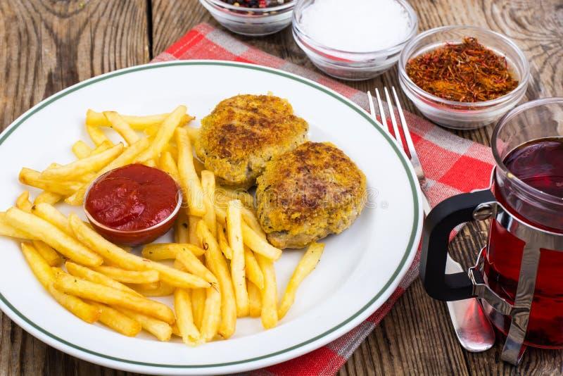 Piatto bianco con le patate fritte e le cotolette della carne sulla tavola di legno immagini stock