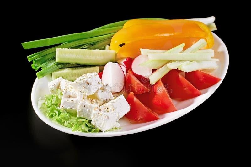 Piatto bianco con le verdure per un'insalata vegetariana fotografia stock libera da diritti