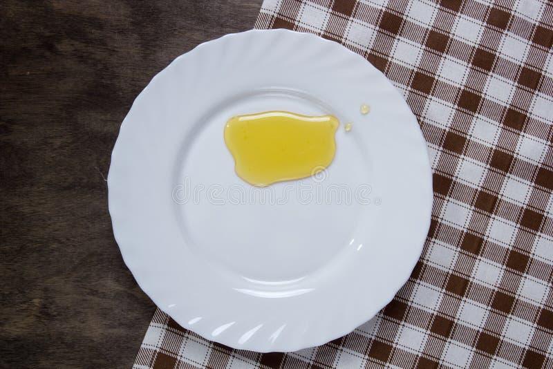 Piatto bianco con miele fotografia stock libera da diritti