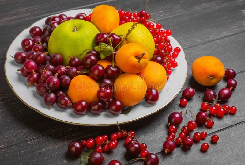 Piatto bianco con un assortimento di frutti freschi e il berrie del giardino fotografie stock libere da diritti