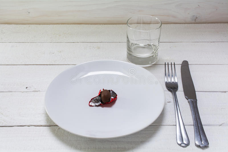 Piatto bianco con un piccolo uovo di Pasqua del cioccolato in stagnola rossa aperta, fotografia stock
