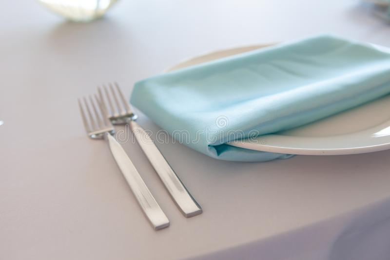 Piatto bianco con un tovagliolo del turchese, una forcella del metallo e un coltello, tavola che fissa nozze immagine stock libera da diritti