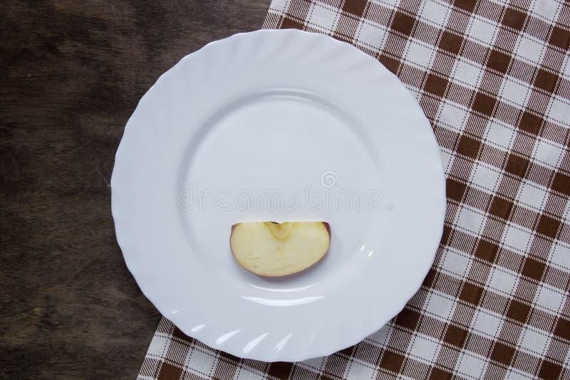 Piatto bianco con una fetta di mela fotografie stock
