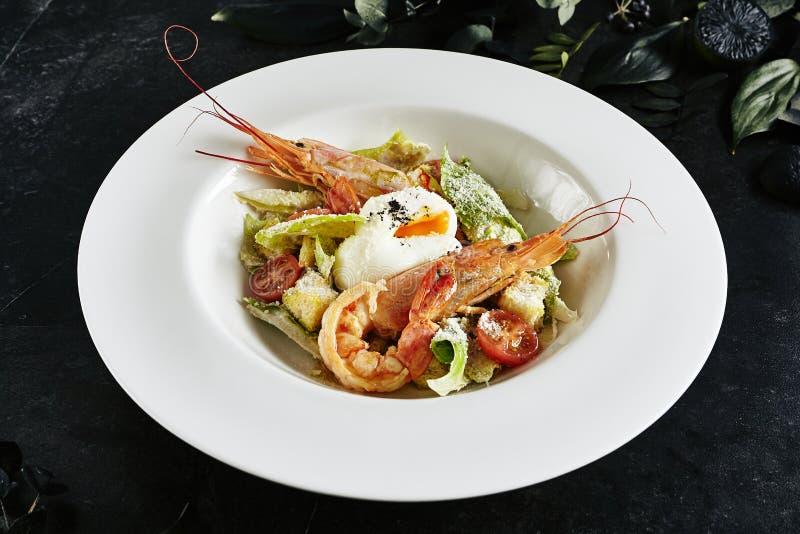 Piatto bianco del ristorante di Caesar Salad con i gamberetti, pollo, crostini, pomodori, vista superiore dei cetrioli fotografie stock