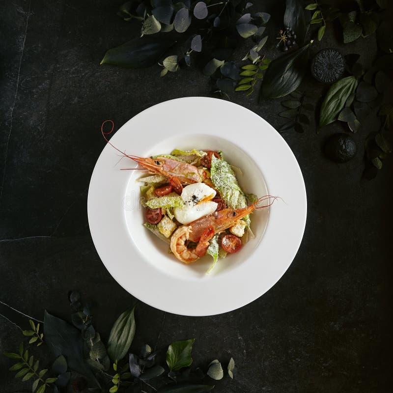 Piatto bianco del ristorante di Caesar Salad con i gamberetti, pollo, crostini, pomodori, vista superiore dei cetrioli fotografia stock libera da diritti