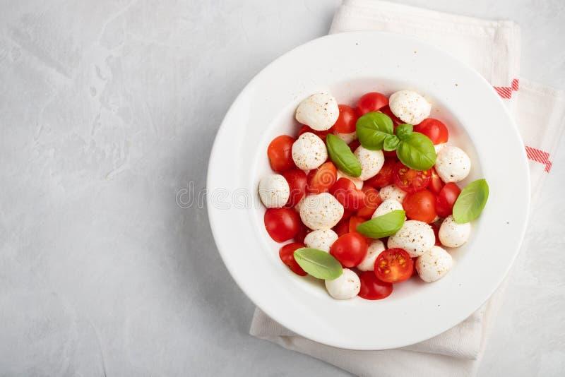 Piatto bianco di insalata caprese deliziosa classica con tomatoe maturo fotografia stock libera da diritti