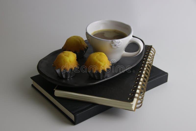 Piatto bianco di Madeleine Cake o con Latte caldo sul piatto ceramico nero fotografie stock libere da diritti