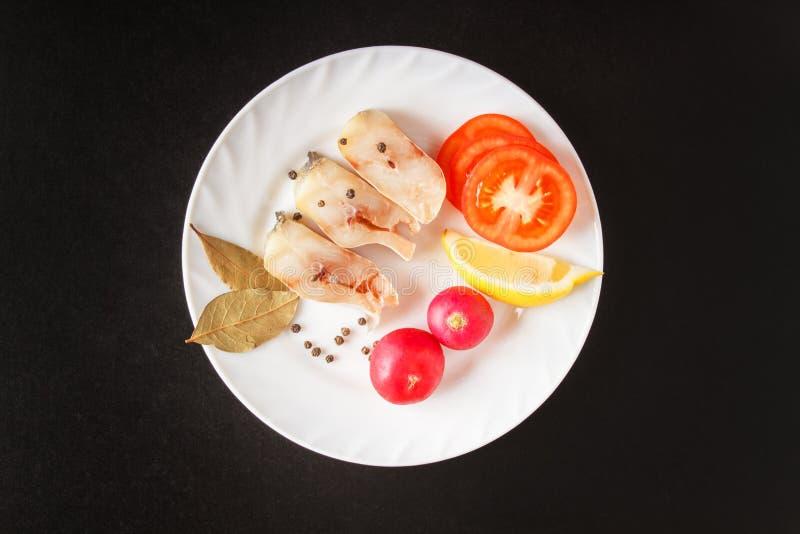 Piatto bianco isolato con gli ingredienti crudi per alimento sano su fondo nero Pesce crudo e vista superiore degli ortaggi fresc immagine stock