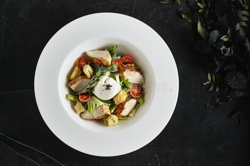 Piatto bianco servente squisito del ristorante del pollo e delle acciughe casalinghi Caesar o Cesar Salad immagine stock libera da diritti