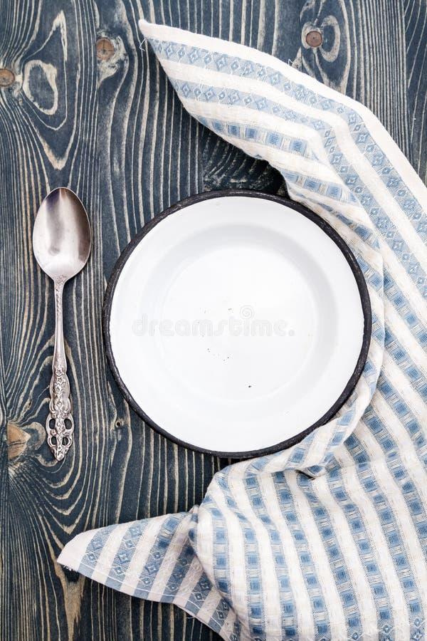 Piatto bianco vuoto dello smalto avvolto con il tovagliolo fotografia stock