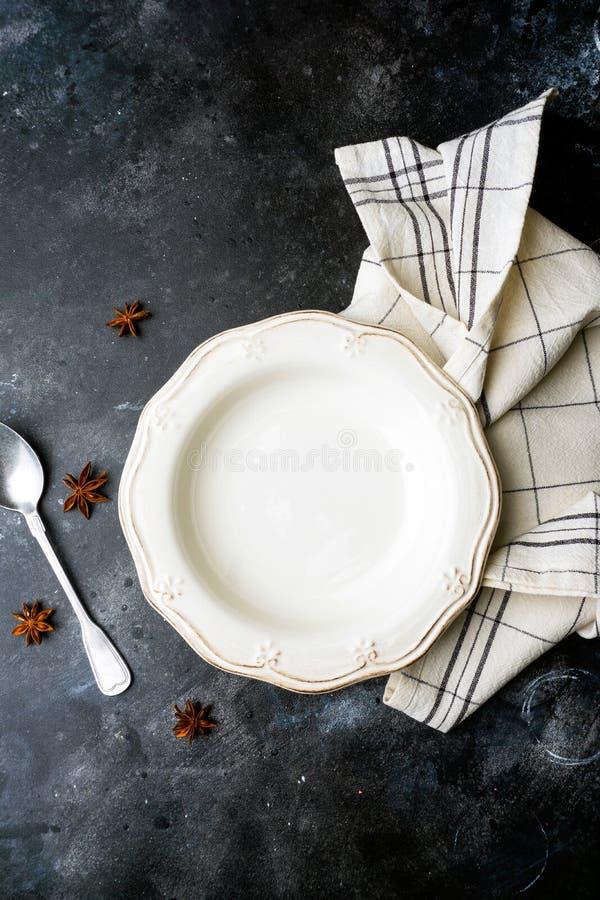 Piatto bianco vuoto su un fondo scuro con un cucchiaio, decorato con un mazzo di lavanda e di un tovagliolo Concetto d'annata dom immagine stock