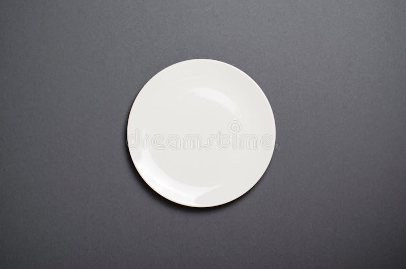 Piatto bianco vuoto, vista superiore su Grey Backround, spazio vuoto fotografie stock