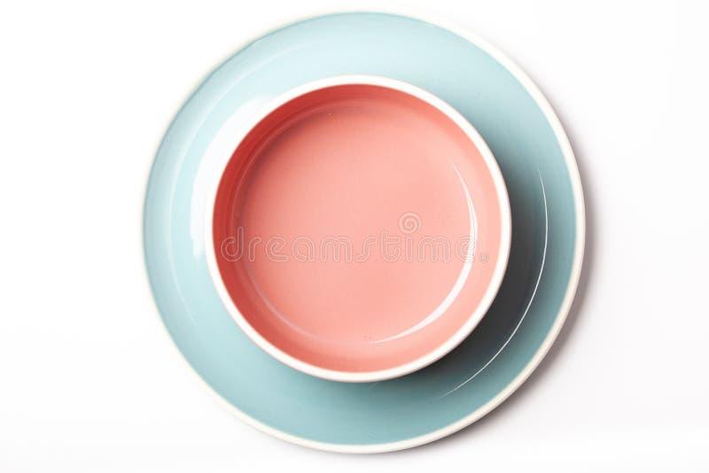 Piatto blu pastello e ciotola rosa su fondo bianco immagine stock
