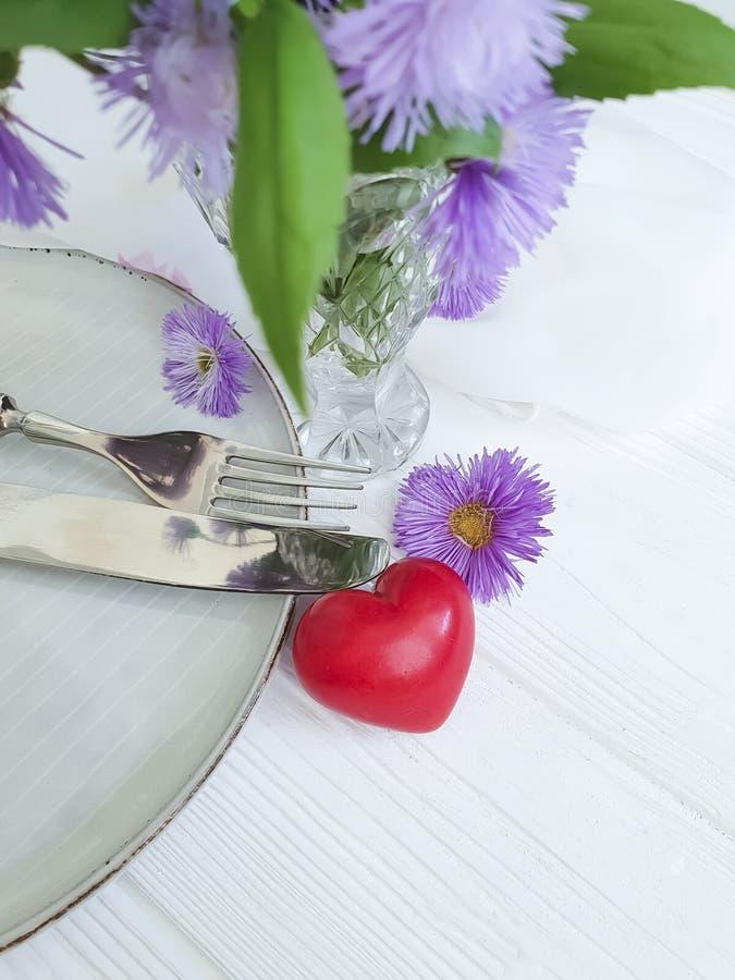 Piatto, cena festiva di celebrazione del cuore della molla del fiore del crisantemo romanzesca su fondo di legno bianco fotografia stock