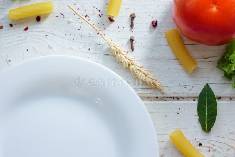 Piatto ceramico bianco circondato dalla pasta italiana di tortiglioni, dalle foglie della baia e da altri ingredienti immagini stock libere da diritti